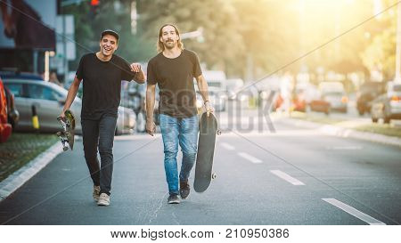 Two Pro Skateboard Rider Walking Down The Street Holding Skateboards