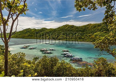 Scenic View Of The Sandbar Of Snake Island In El Nido, Palawan With Some Boats Full Of  Tourists.