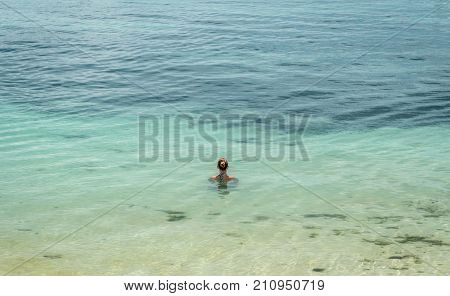 A beautiful woman relaxes immersed in the sea Alona Beach Panglao Philippines
