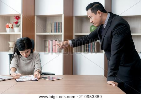 Asian secretary stresses when her manager is pointing and being blamed for a faulty job. Secretary and Manager in office.