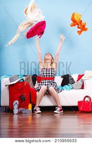 Cleaning in the closet packing for travel fashion happiness concept. Woman sitting on sofa throwing up lot of clothes. Clothing flying all over the place