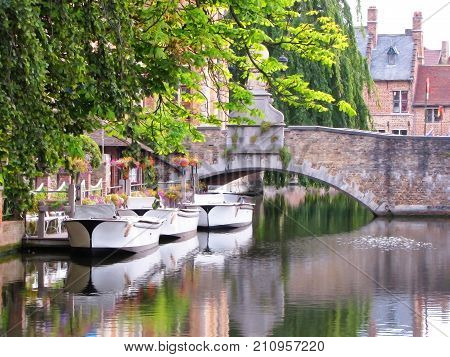 Three Boats sit in Canal Waterway in Bruges, Belgium