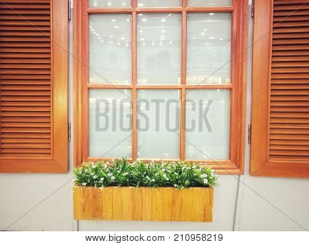 Brown wood window and the glass inside with wood box for planting small trees in front ofIt is perfect and creative design vintage and modern blend.An ideal example for who loves home office decor.