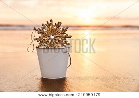 Golden Christmas Snowflake Collected in a White Bucket at Sunset on the background of Beach and Sea in California