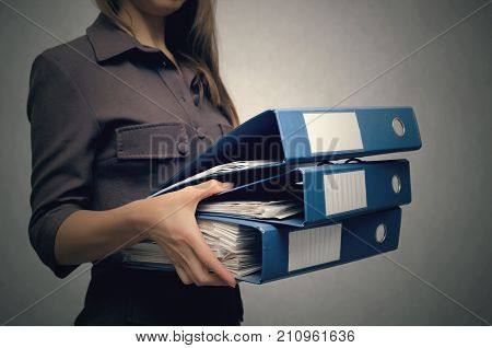 Business woman holding a stack of folders for documents in front of her close up. Overworked woman concept. Documents work. Secretary.