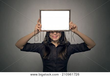 Grateful letter. Gratitude concept. Accolade. Thank letter. Special offer. Young business woman hiding behind blank photo frame holding in her hands. Appreciation document.