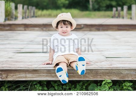 Closeup happy asian kid with smile face sit at wood pathway in the park background