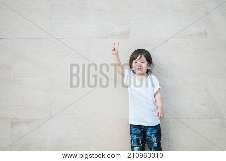 Closeup asian kid with hold up 2 finger in fighting means on marble stone wall textured background with copy space