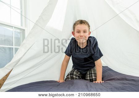 Young boy in his fort made from sheets