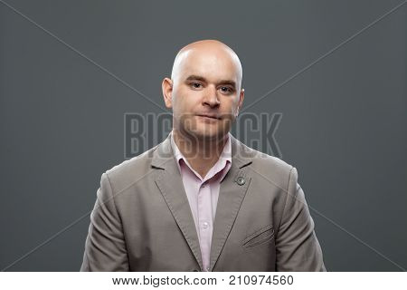 Portrait of caucasian bald man on the dark background. Studio shoot.