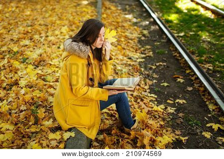 A Beautiful Happy Brown-haired Woman In A Yellow Coat And Jeans Sits Alone In The Park Near The Tram