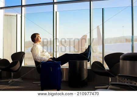 Caucasian man in early fifties side profile sleeping with legs up in airport terminal airplanes in background on tarmac