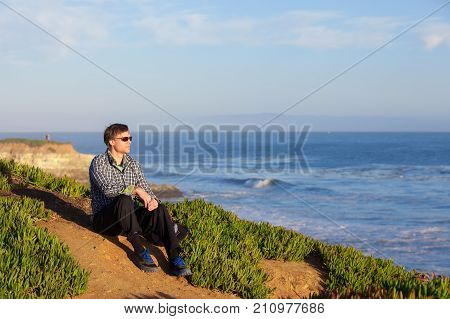 Caucasian man in early fifties relaxing on hill overlooking the ocean with waves in background