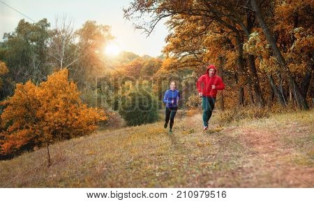 A coupe of athletes in black leggins and color jacket run on a jogging on the colorful autumnal forest hill.