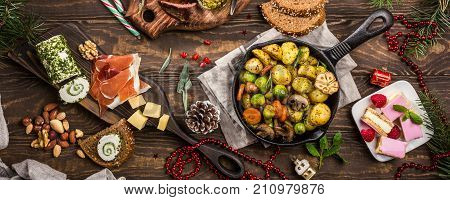 Banner of Delicious Christmas themed dinner table with roasted meat steak, appetizers and desserts. Top view. Holiday concept.