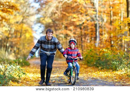 Little preschool kid boy and his father in autumn park with a bicycle. Dad teaching his son biking. Active family leisure. Child with helmet on bike. Safety, sports, leisure with kids concept.