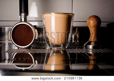 Barista equipment for making coffee and cup of coffee on the light background of coffee machine