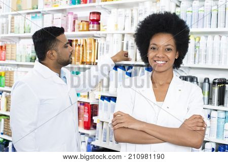 Pharmacist Standing Arms Crossed While Colleague Arranging Produ