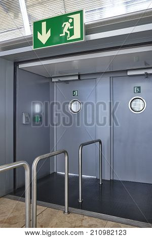 Airport emergency exit way out way metallic doors. Alert sign