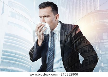 Feeling ill. Serious moody young businessman holding a paper tissue and coughing while feeling ill