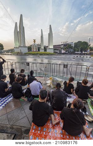BANGKOK THAILAND - OCTOBER 26: Unidentified people sit next to Democracy Monument for the cremation of Rama 9 the former king in Bangkok Thailand on October 26 2017.