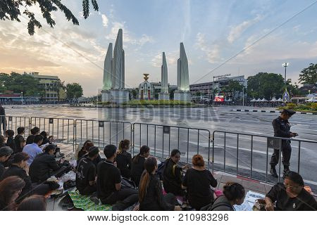 BANGKOK THAILAND - OCTOBER 26: Unidentified people sit next to Democracy Monument in the late afternoon for the cremation of Rama 9 the former king in Bangkok Thailand on October 26 2017.