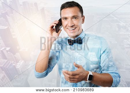 Phone discussion. Happy handsome positive man putting his phone to the ear and smiling while having a pleasant conversation