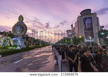 BANGKOK THAILAND - OCTOBER 26: Unidentified mourners in black walk near Ratchadamnoen Avenue for the cremation of Rama 9 the former king in Bangkok Thailand on October 26 2017.