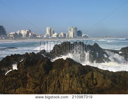 WINTER SEASCAPE, WITH WHITE WAVES WASHING OVER SOME ROCKS IN THE FORE GROUND AND HIGH RISE BUILDINGS IN THE BACK GROUND 01ii
