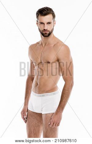 Confident stunning man. Handsome shirtless young man in white pants looking at camera while standing against white background.