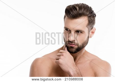 Portrait of perfect stubble man. Portrait of handsome shirtless young man looking away while standing against white background.