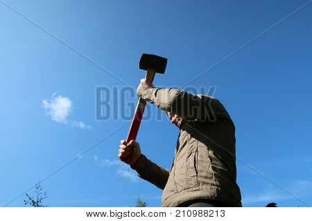 man with raised sledgehammer on blue sky background