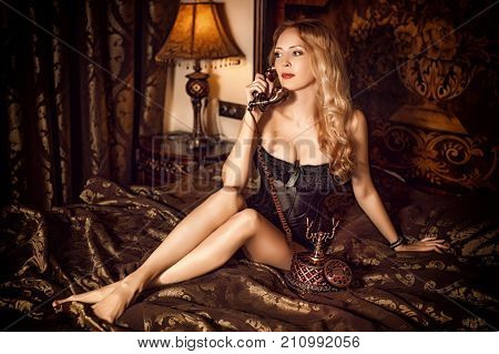 Aristocratic beautiful woman wearing corset speaking by vintage phone and sitting on luxury retro bed