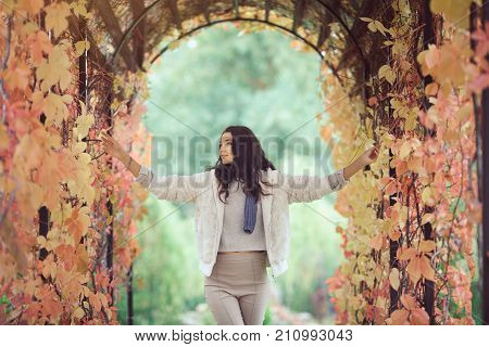 Autumn girl playing in city park. Fall woman portrait of happy lovely and beautiful mixed race Asian Caucasian young woman in garden arch in fall colors. Model in white casual clothes looking smiling toching leaves and looking at nature beauty.