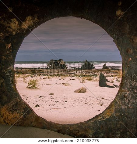 The wreckage of a historic WWII shipwreck viewed through a porthole on a piece of steel.  Cape Point, South Africa.