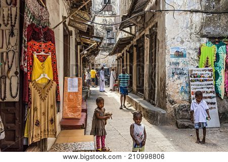 STONE TOWN, ZANZIBAR - OCTOBER 24, 2014: Local people on a typical narrow street in Stone Town. Stone Town is the old part of Zanzibar City, the capital of Zanzibar, Tanzania.