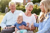 Grandparents Sit Outdoors With Baby Grandson And Adult Daughter poster