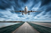 Airplane and road with motion blur effect in overcast. Landscape with passenger airplane is flying over the asphalt road and cloudy sky. Commercial plane is landing. Aircraft with blurred background poster