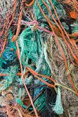 A tangled mess of fishing nets plastic rope and other debris washed up on a coastal beach ideal for an ecological hazard or pollution concept poster