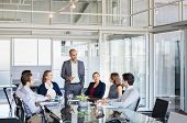 Human resource manager training people about company and future prospects. Group of businesspeople sitting in meeting room and listening to the speaker. Leader man and work group in a conference room. poster