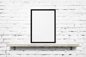 White blank photo frame mockup on shelf over white brick wall background
