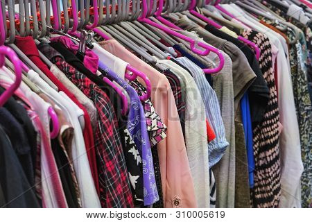 Various Women Clothing On Mostly Pink Coat Hangers Inside Charity Second Hand Thrift Shop