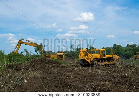 Bulldozer And Excavator Used To Dig Up Tree-stumps And Roots After The Forest Was Removed. Mechanica