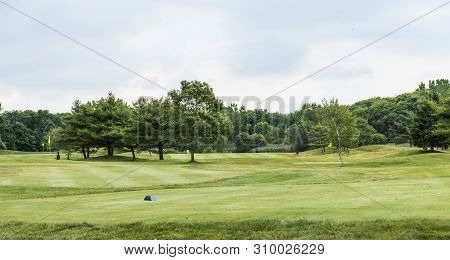 The Lanscape Of A Par Three Golf Course With Trees And Three Yellow Flags On Small Greens.