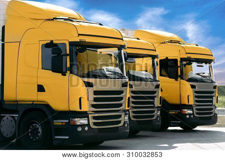 Three Yellow Trucks Of A Transporting Company Parked In Row In The Parking Lot. Trucking And Logisti