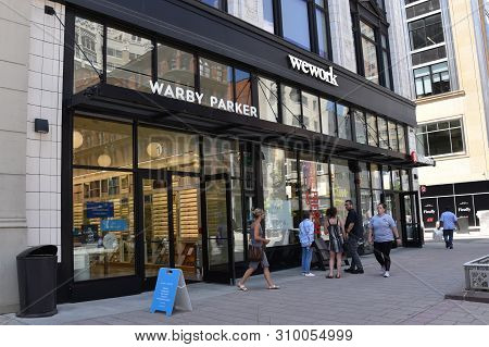 Detroit, Mi / Usa - June 30, 2019:  People Walk Past The Warby Parker Store And Wework Coworking Spa