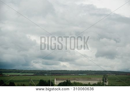 Dark Dramatic Rainy Sky Clouds Over Train Composition In Rural  Farm Landscape, Bad Weather In Summe