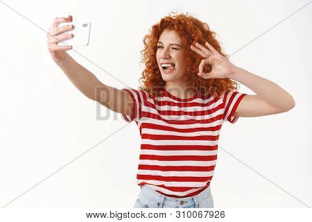 Good-looking Redhead Curly Fashionable Female Blogger Mimicking Taking Selfie Extend Arm Smartphone