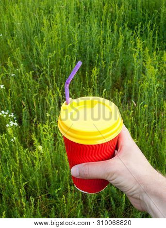Hand Holding Bright Red Plastic Cup With Yellow Lid And Purple Bendy Drinking Straw (tube) Against T