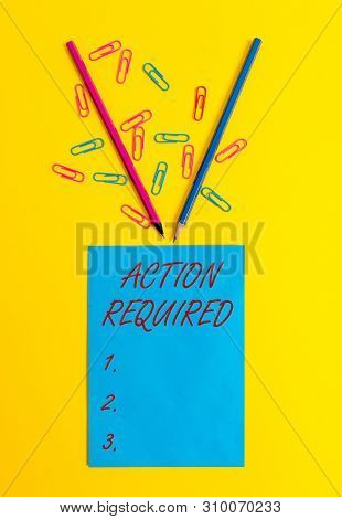 Word writing text Action Required. Business concept for Regard an action from someone by virtue of their position Blank paper sheet message reminder pencils clips colored background. poster